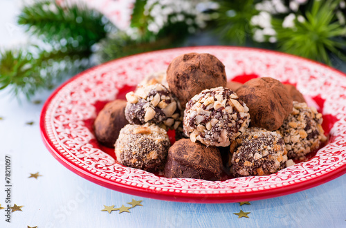 Assorted dark chocolate truffles on red plate