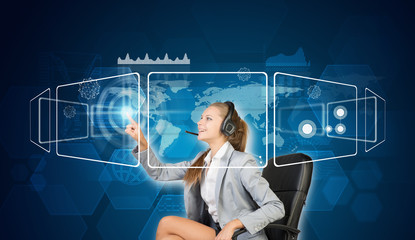 Businesswoman in headset using touch screen interfaces