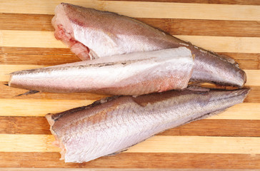 frozen fish hake on cutting board background