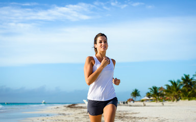 Cheerful woman running at tropical beach