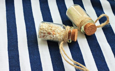 corked bottles with sand on marine clothing