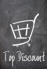 top discount text and shopping cart sign on blackboard