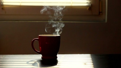 hot cup of morning coffee illuminated by sunlight