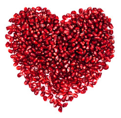pomegranate seeds in a heart-shaped  isolated on a white