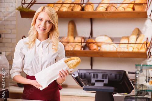 Plexiglas Bakkerij Beautiful young shop assistant in a bakery