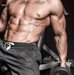Sexy sportsman with dumbbells in gym