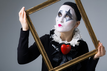 Woman in disguise harlequin in the picture frame