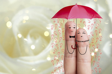 Finger art. Couple is embracing and holding red umbrella