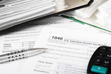 U.S. Individual tax form 1040 with calculator and pen.