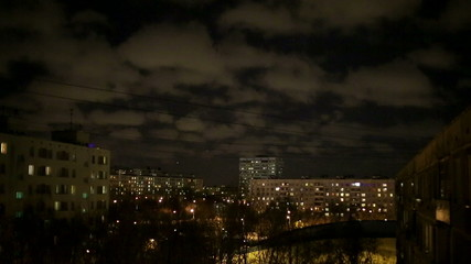 Sky over the city at night, racing clouds