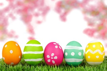 Colorful painted Easter eggs on grass with pink cherry blossoms