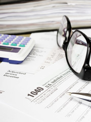 U.S. Individual tax form 1040 with glasses, calculator and pen.