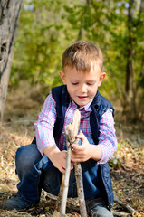 Cute Little Boy Playing with Sticks at the Woods