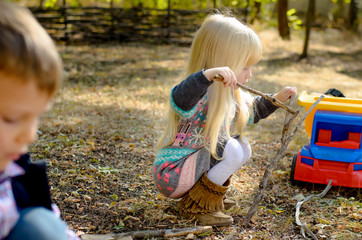 Little Blond Girl Playing Sticks on the Ground