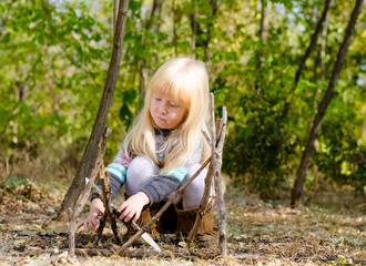 Serious Blond Girl Assembling Sticks on the Ground