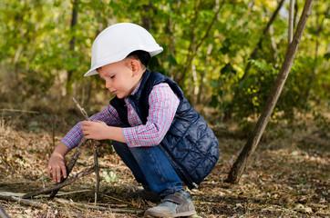 Sitting Little Boy with Helmet Playing Sticks
