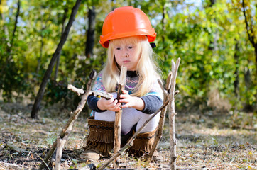 Little Girl with Helmet Playing with Sticks