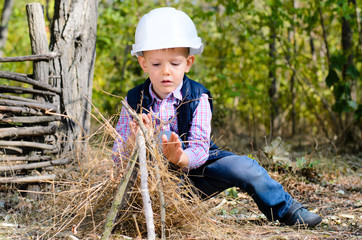 Sitting Little Boy with Helmet Playing Sticks