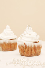 White cupcakes with decorative silver sprinkles. Shallow dof.