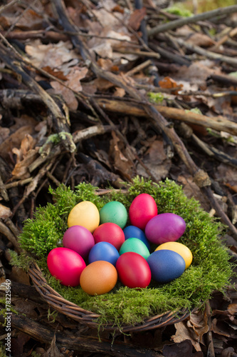 Colored eggs in a basket - 78225649