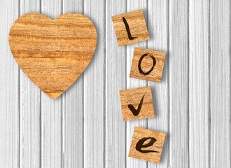 Wood heart on white wooden background. Love cast out of wood kub