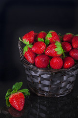 Strawberries in a basket on a black background.
