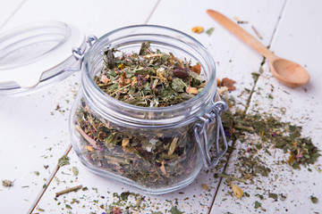 Glass container with herbal tea on white table