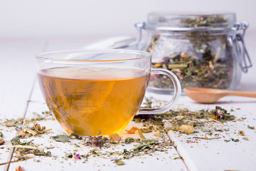 Cup of herbal tea with glass jar