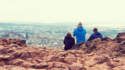 Friends taking photos of Edinburgh on top of hill using phone
