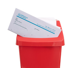UK tax return in red plastic rubbish bin. Tax avoidance, evasion