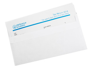 UK tax return in envelope isolated on white.