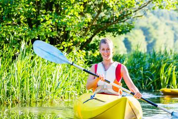 Frau fährt im Kajak auf Wald Fluss