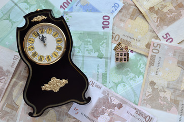 Money, a clock and a house