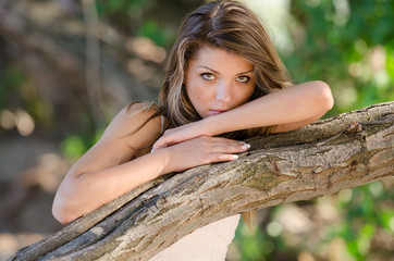 Nostalgic moments of a beautiful girl, she rests on a tree trunk