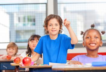 Elementary school multi ethnic classroom. Kid ready to answer