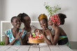 Girl looking at birthday cake surrounded by friends - 78229607