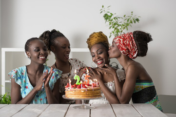 Girl looking at birthday cake surrounded by friends