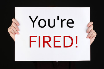 Sheet of paper with text You're Fired in hands isolated on