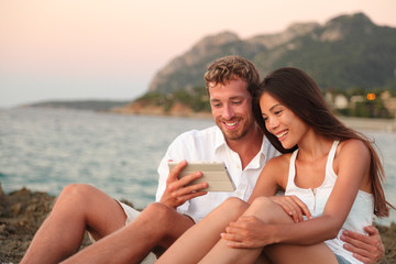 Romantic couple relaxing on beach using tablet app