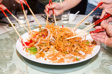 Tossing and mixing Yee Sang during Chinese New Year meal