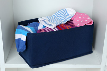 Different socks in textile box on closet background