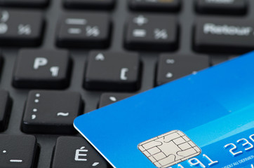 Blue credit card on black keyboard closeup studio shot