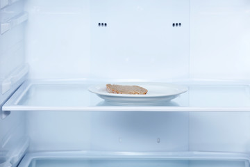 Piece of bread on plate in refrigerator