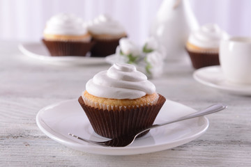 Delicious cupcakes on table on light background