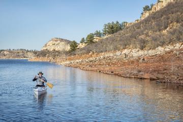 senior male paddling canoe