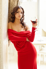 Brunette posing in sexy dress with glass of wine