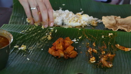 white man eats indian rice with flat cake from banana leaf as th