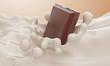 Leinwandbild Motiv The piece of chocolate falling in a milk stream and splash