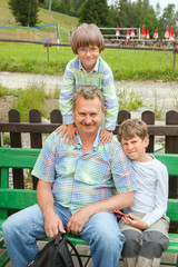 the grandfather of two grandsons sit on bench
