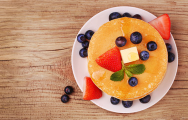 Pancakes with fresh blueberry and strawberry on wood background